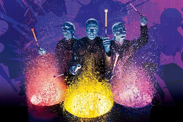 Blue Man Group performing a musical number with colored paint and drums at Universal Orlando.