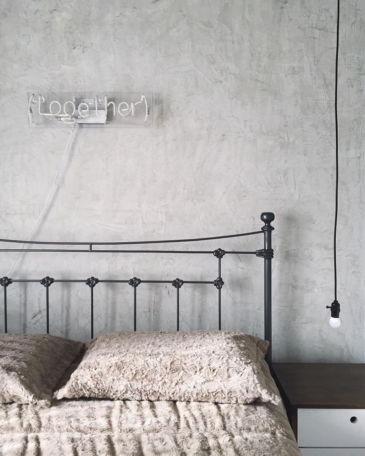 Quarto com parede de cimento queimado, lustre iluminado e cama simples