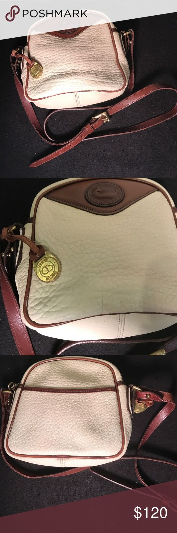 """1982 Vintage Dooney & Bourke crossbody This is an All Weather Leather vintage Dooney & Bourke crossbody. Purse is vintage and in EUC. It has the blue and red cloth tag that says Dooney & Bourke and Made in USA. The fob is the backwards D & a B. Date code reads A7 204877 which based on my research means this purse was made in 1982. It is taupe with burnt cedar trim. Measures: 7.5"""" tall, 8"""" wide and 2.5"""" deep. Strap drop is 19.5"""" with the ability to add 4 more inches if adjusted. Interior has…"""