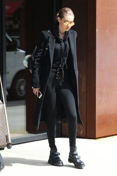 Gigi Hadid wearing Dr. Martens Coralia Adjustable Strap Boot, Are You Am I Strike Leggings, Are You Am I Strike Hoodie, Linda Farrow 427 C1 Oval Sunglasses in Yellow Gold, Versace Medusa Backpack and Winonah Wool Blend Overcoat