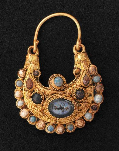 """The Cologne Earring. 11th c. in an cesspit of the medieval Jewish quarter. Gold, richly ornamented with gemstones, pearls and an antique dark blue Roman cameo depicts a warrior, clear similarities to the work of goldsmiths at the imperial court. """"lunula"""" or three-quarter moon shape. unusual details to conclude that is a unique piece. alternation of turquoise-coloured glass beads with pearls and dark red glass. From the early to the high Middle Ages, glass was an extremely valuable material."""