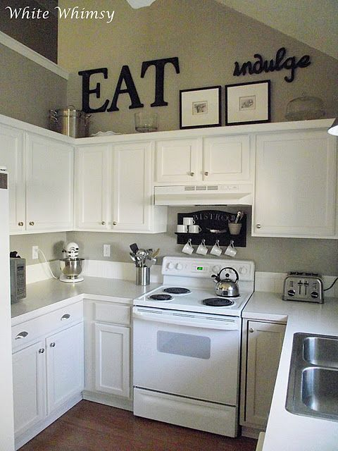 Simple words like 'eat' and 'indulge' make a bold statement above these cabinets.