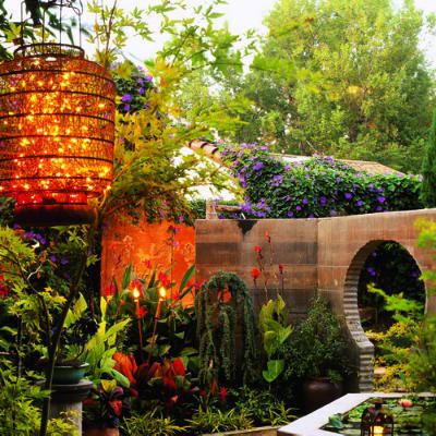 Chinese lanterns stuffed with sparkling white lights dangle from arbors. A large dining patio radiates a warm glow from the back of the garden. And a dramatic fiery orange light bathes an ancient-looking wall relief.