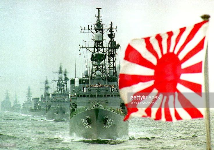 The flag of the Rising Sun, formerly used by the Japanese Imperial Navy and now used by the Japan Maritime Self Defense Force (MSDF), flutters in the wind while a fleet of the MSDF makes its way in Sagami Bay, south of Tokyo, during a fleet review to mark the 40th anniversary of the MSDF's founding 11 October, 1992. About 55 ships and 53 aircraft participated in the fleet review.