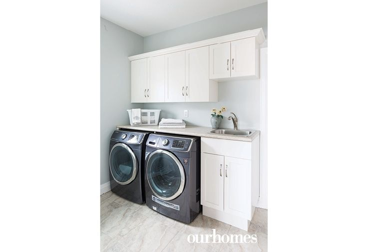 A bright laundry room just off the kitchen houses an energy-efficient washer and dryer set. - Via OUR HOMES Wellington Spring 2016.  http://www.ourhomes.ca/articles/build/article/the-rain-and-the-sun-power-this-gorgeous-elora-home