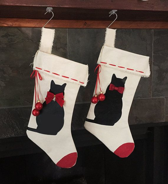Christmas Cat Stocking  Even kitties need a Christmas stocking and this one is purrfect for your feline family member or cat lover!  This hand-sewn, sturdy canvas stocking measures roughly 14 inches tall by 6 inches wide in the middle. It features a black cat silhouette cut from high quality heat transfer vinyl, wearing your choice of either a Christmas bow with a bell or a sweet little bowtie. A red ribbon is woven around the top and either glossy, glittering or matte Christmas ornaments…