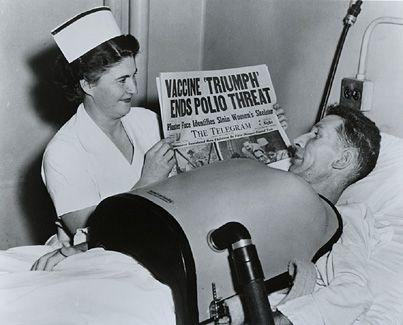 Photo of a nurse holding up a newspaper with the heading Vaccine Triumph Ends Polio Threat for a man using a chest respirator