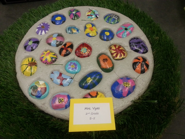 Stepping Stone.  Each student designed and painted their individual river stones.  They were then dried into a cement base.  2nd grade class.