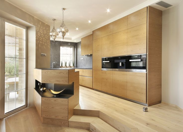 Light wood modern step up kitchen with sleek appliances by Hans Krug