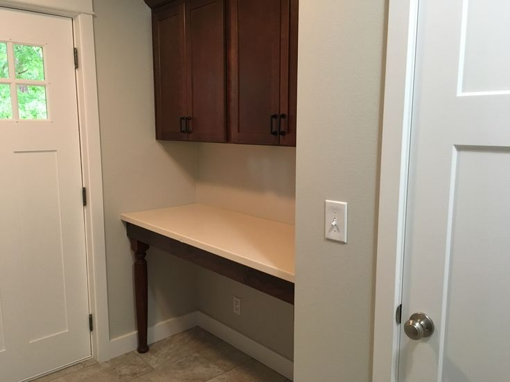 Large folding table and utility closet in new laundry room.