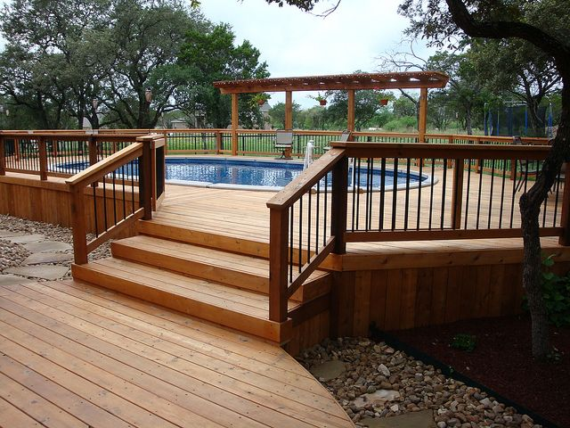 above ground pool with deck and pergola.
