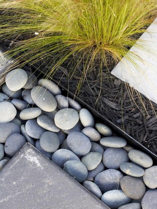 """Gros galets gris clair, graminées et paillis d'ardoise foncée (trouver sous forme de """"grandes aiguilles"""") forment une association largement plébiscitée sur les sites spécialisés"""