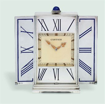 A SILVER TRAVEL CLOCK, BY CARTIER  Designed as a triptych, the rectangular reeded case opening to reveal a square cream dial within a broad silver bezel with blue enamel Roman numerals and lapis lazuli pushpiece, 1950s, 8.4 cm high, with London hallmarks for silver, in red leather Cartier case Dial signed Cartier, case with No. .4422.