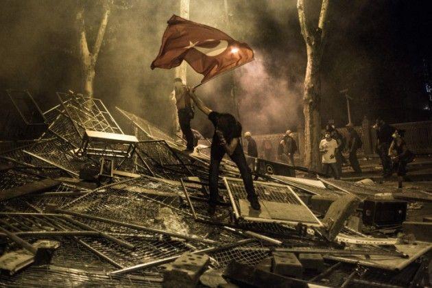 FOTOGRAFIA Daniel Etter. Estambul, Turquía. Junio 1, 2013. Jóvenes de enfrentan con policías cerca de la oficina del Primer Ministro en el Palacio Dolmabahce. Los protestantes avanzan hacia las oficinas y la policía arremete con cañones de agua y cantidades enormes de gas lacrimógeno. En una de las barricadas un hombre agita una bandera turca, colapsándose por el gas lacrimógeno.
