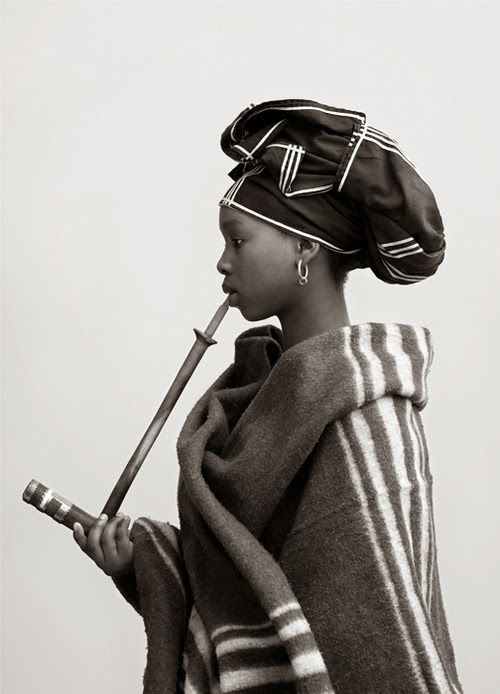 Xhosa young woman, bur she's not supposed to have a pipe until menopause.
