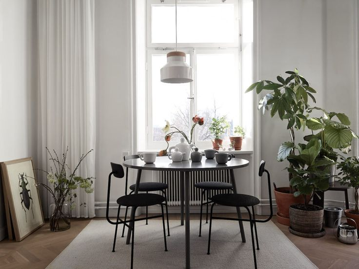 Dining table, round and grey. Black chairs, Afteroom, from Menu. Green plants and art. Curtains. Scandinavian interior inspiration and decoration. The home of Jonas Wagell.