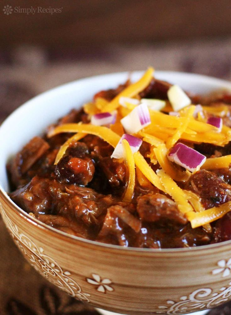 Chili con Carne! With chunks of chuck roast, browned in bacon fat and cooked with red kidney beans, red chili and chipotle chili, onion, garlic, jalapeños, tomatoes, and lime juice. Top with grated cheddar and chopped red onion. So GOOD!!! On SimplyRecipes.com