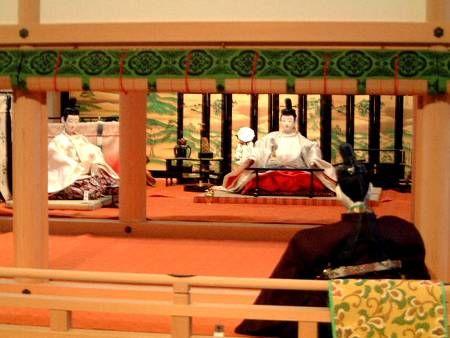 京都市下京区にある風俗博物館のこと。2002年2月中旬に風俗博物館を訪ねて撮影した展示の様子です。寝殿では、六條院行幸の場面が展示されていました。『源氏物語』<藤裏葉>と<胡蝶>を参考に設営されたのだそうです。展示の様子、全景。冷泉帝<天皇>と朱雀院<上皇>が光源氏の邸宅・六條院にお出ましになられました。池に浮かべられた龍島鷁首(りゅうとうげきす)の舟の上では童たちによる「胡蝶(こちょう)」・「迦陵頻(かりょうびん)」の舞が行われました。簀子(すのこ)には束帯姿の上達部、殿上人たちが一日晴れの据(いちにちばれのきょ)を高欄(こうらん)から垂らしています。重要文化財「駒競行幸絵巻」(和泉市久保惣記念美術館所蔵)の絵を参考にされているようです。南庭には、楽人たちが居並んでいます。母屋中央には御引直衣(おひきのうし)...