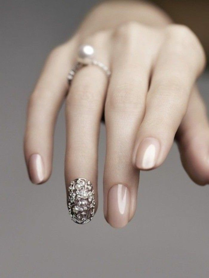 slim hand with long fingers and a pearl ring, fingernails painted in nude polish, one fingernail has decoration with metal details