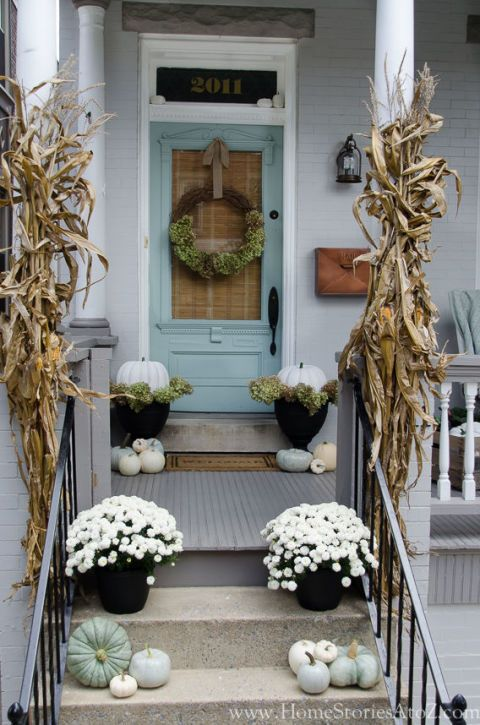 A soft gray and muted blue color palette is especially gorgeous in the fall, where it works with nearly all the hues of autumn. Beth of Home Stories A to Z added ivory-hued pumpkins and white mums, which work harmoniously with the sophisticated exterior. Click through for a tutorial and more fall porch decorations.