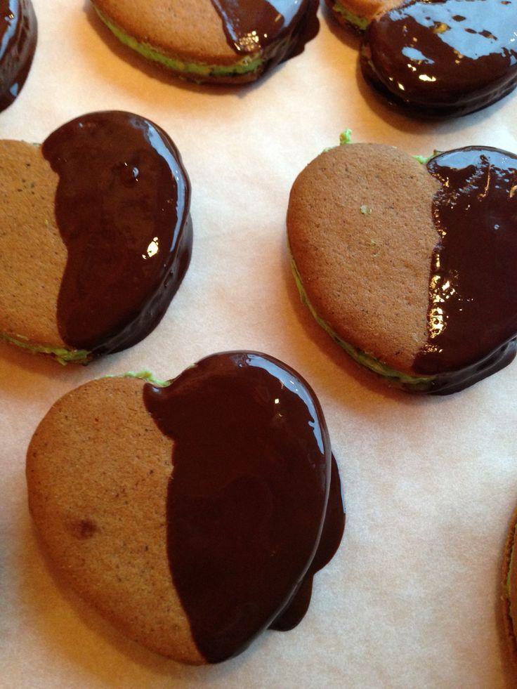 Pistagesmörkräms fyllda pepparkakor som är doppade i mörk choklad