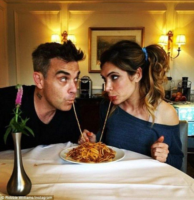 The look of love: Robbie Williams, 42, and Ayda Field, 37, put a smile on many of their fans' faces as they recreated the famous spaghetti eating scene from the Disney classic Lady And The Tramp