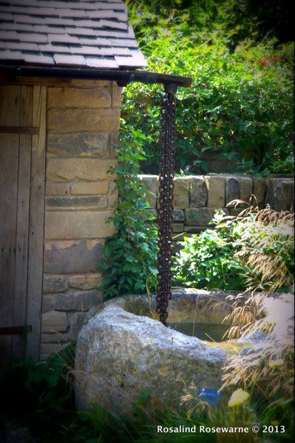 Rain chains  falling into a rustic stone pool. The dry garden captures as much water as it can