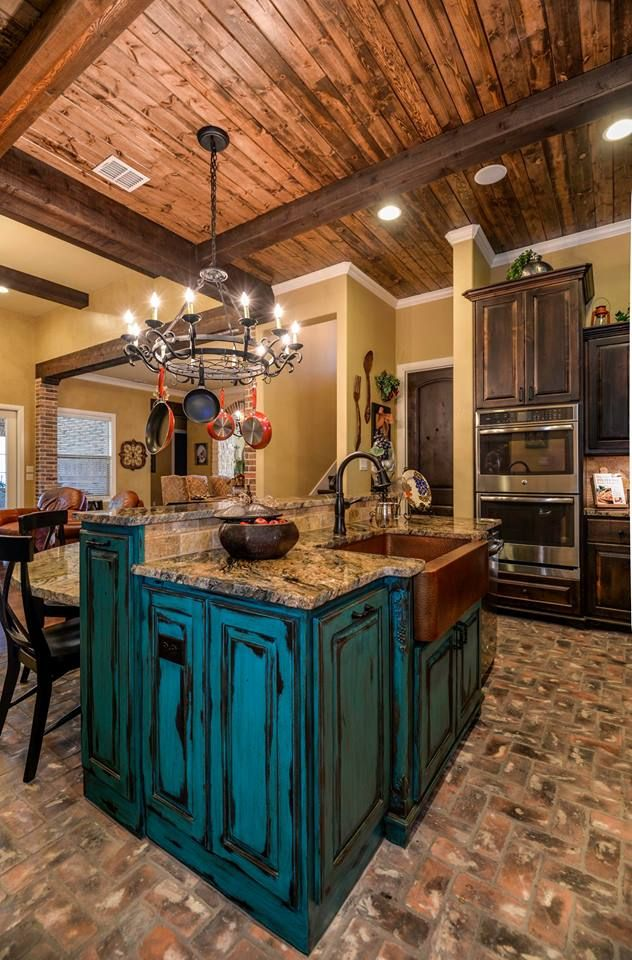 Tuscan design.. Turquoise distressed island with granite counter tops.  Brick flooring, Knotty Alder cabinets and wood ceiling.  Contact Todd Homes for more details. 979-704-6102 www.toddhomes.com