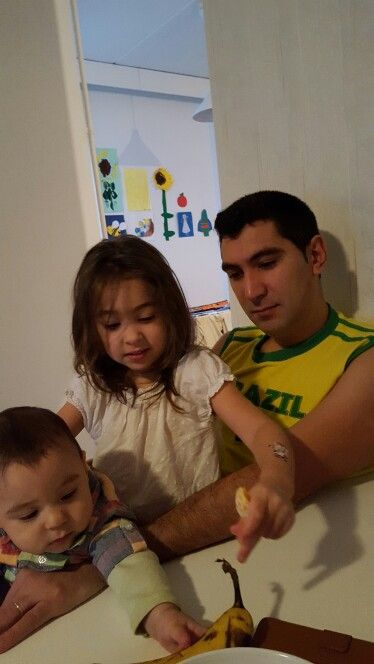 They're all looking pretty intrigued with that banana. . Daddy's lap.