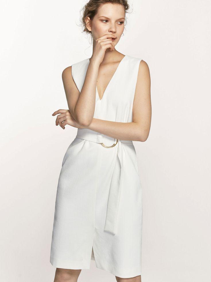 Sukienka z paskiem i obręczą, o taliowanym kroju, z dekoltem w szpic, zapinana na suwak z boku, bez rękawów, z rozcięciem z przodu, na podszewce. Długość sukienki w rozmiarze 38 wynosi 96,7 cm.