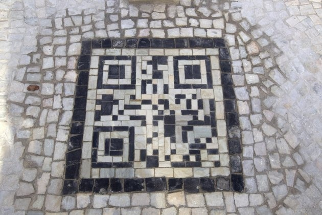 A two-dimensional bar code, or QR code, as they're known, made from black and white stones covers a sidewalk near the beach in Rio de Janeiro, Brazil, Friday, Jan. 25, 2013. The QR codes are being placed at tourist spots which can be scanned with a mobile device for information about the site. (AP Photo/Silvia Izquierdo)