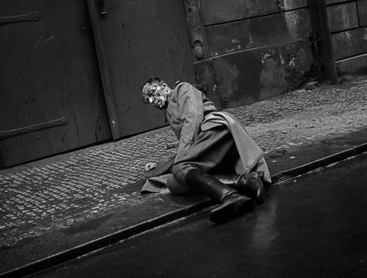 A battered German officer sits on the pavement during the Prague Uprising. WW2