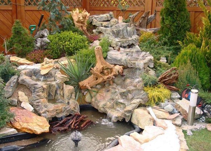 cascade de bassin décorative en pierre naturelle décorée d'arbustes conifères et de plantes vivaces