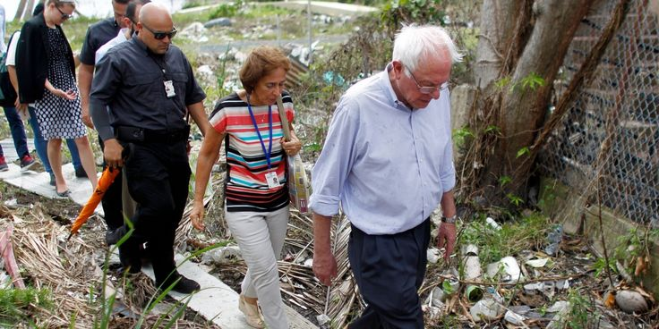 US Sen. Bernie Sanders (I- VT) walks over debris caused by the passing of Hurricane Maria through the area during a visit with the Mayor of San Juan Carmen Yulin to the Playita community in San Juan, Puerto Rico, on October 27, 2017.More than 73,000 people have fled emergency conditions at home for Florida since Hurricane Maria devastated the US territory in the Caribbean. / AFP PHOTO / Ricardo ARDUENGO (Photo credit should read RICARDO ARDUENGO/AFP/Getty Images)