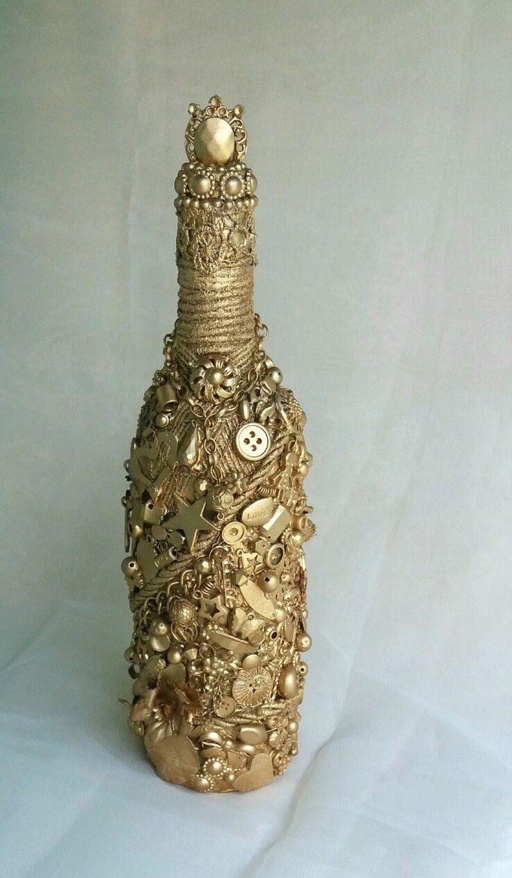 Garrafa decorada com pequenos objetos e pintada com tinta spray dourada