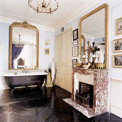 La salle de bains est équipée d'une cheminée en marbre, d'une baignoire en fonte à l'ancienne et d'un sol teinté noir.