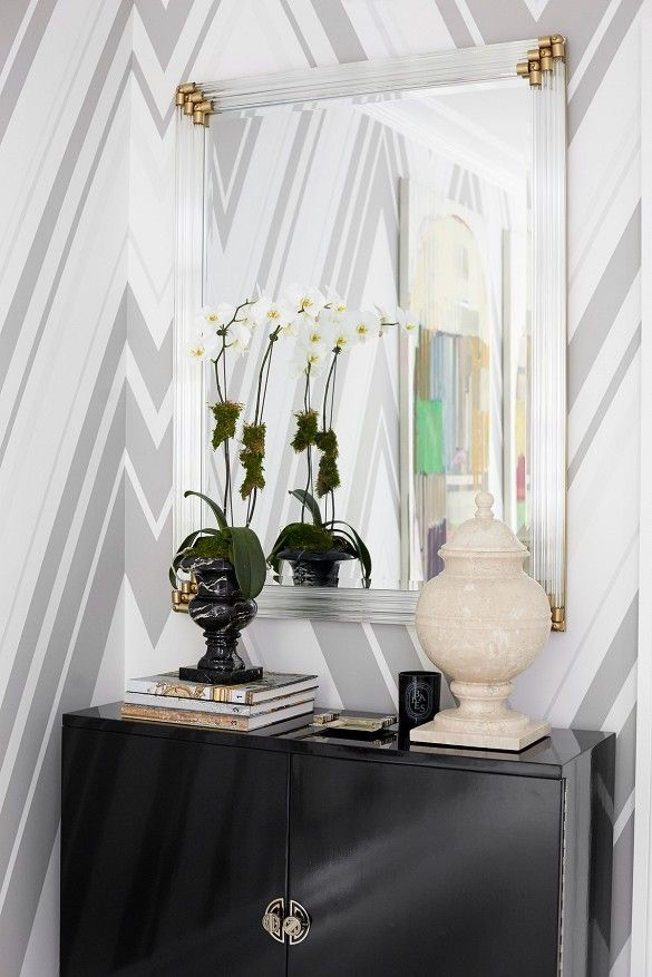 Black cabinet with lucite and brass mirror and chevron wallpaper.