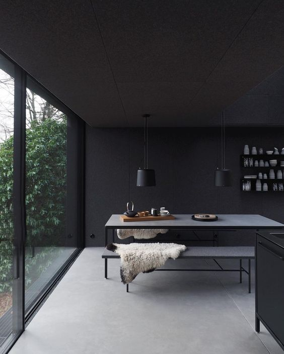 Black kitchen with polished concrete floor and full height black metal framed sliding door. Dream kitchen.