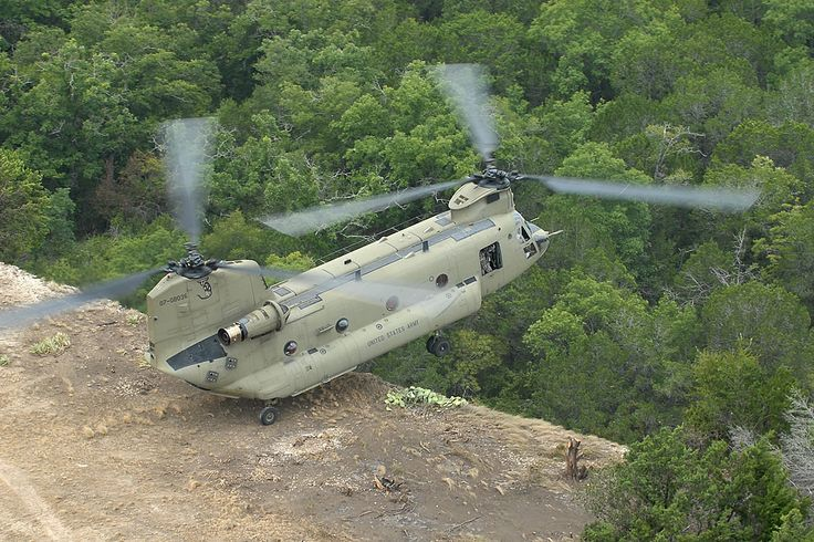 US Army Boeing CH-47F Chinook doing troop drop off on cliff top.
