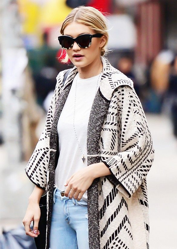 Gigi Hadid wore a white shirt with relaxed boyfriend jeans, a printed oversized cardigan, a long pendant necklace, and sunglasses.