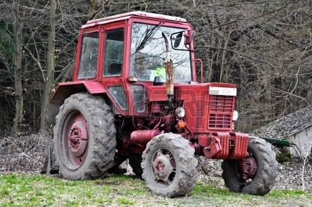 Dirty red tractor in the woods Stock Photo