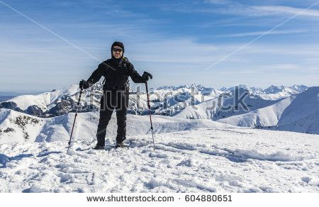 Hiker with trekking poles and backpack on a background of mountain peaks in winter scenery.