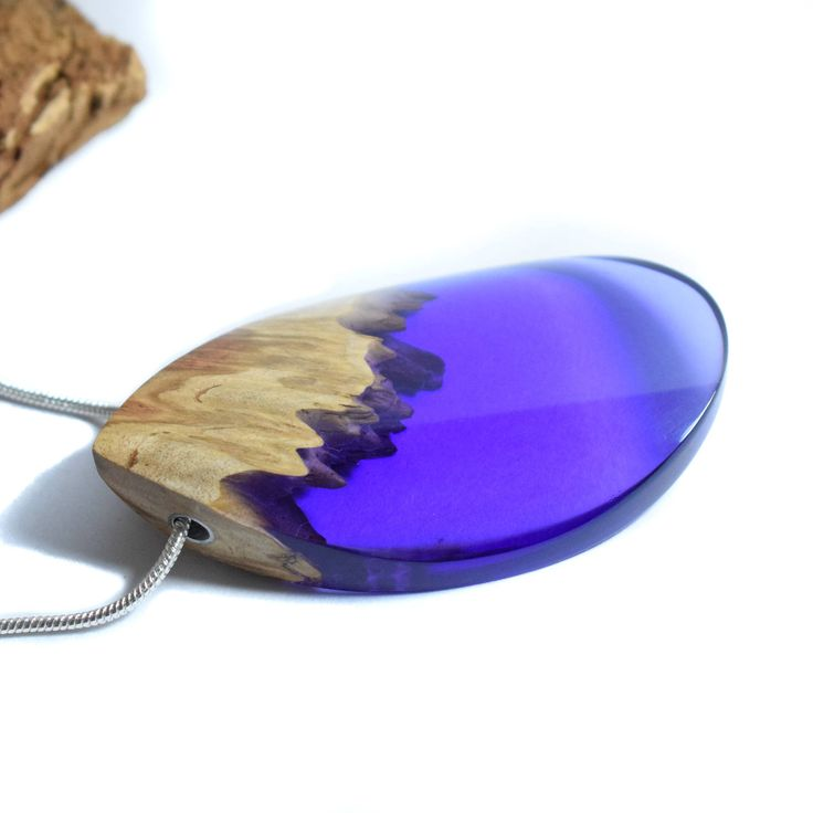 ArtfulResin handmade purple pendant, made by me in Kent, United Kingdom. This stunning wood resin necklace is a fusion of burl wood and purple resin. Feel closer to nature when you wear this pendant! This modern necklace has a natural and ethereal feel to it combined with beautiful boho chic design. We have used an aluminium finding for extra durability and strength. It is finished off with a silver plated snake chain with a lobster clasp. The resin is ultra clear and it is polished to a…