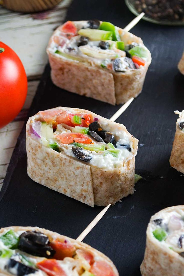 These Greek tortilla pinwheels are a great idea for a party. Spread feta and yogurt on a tortilla, sprinkle with Greek toppings, then roll and slice!