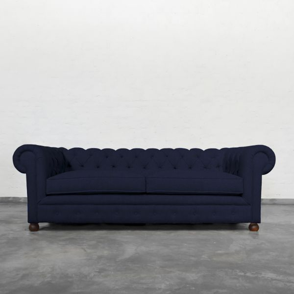 Chesterfield Indigo: The Chesterfield conjures visions of English libraries or men's clubs, with its tufted back, high rolled arms, and tufted facade. Our take on this classic brings in enormous charm to your living room with this beautifully handcrafted masterpiece by one of our 4th Generation sofa artisans.