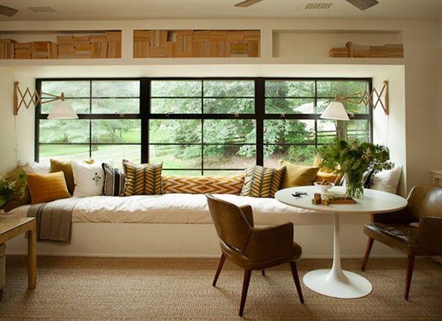Sofá aconchegante e branco na janela, com almofadas e janelas grandes com esquadrias pretas