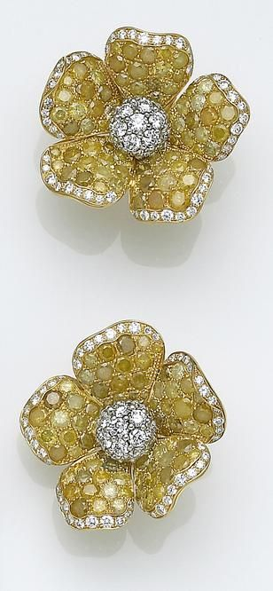 A pair of colored diamond, diamond and eighteen karat gold earrings designed as flowers, each centering a bombé form set with round brilliant-cut diamonds, the petals set with yellow round brilliant-cut diamonds; estimated total diamond weight for the pair: 25.00 carats.