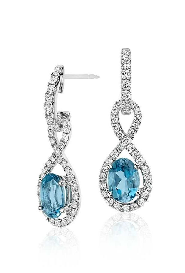 These contemporary drop earrings feature beautiful oval aquamarine gemstones set within a brilliant diamond infinity twist design.