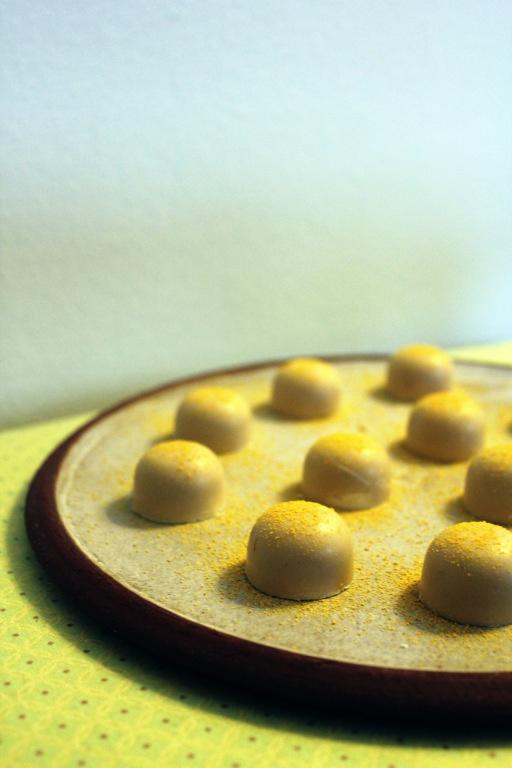 Fyldte chokolader med passionsfrugt og havtorn     300 gram hvid chokolade af god kvalitet     Frysetørrede havtorn     6 passionsfrugter     Saften fra 1/2 appelsin     100 gram sukker     3 hele æg     50 gram smør     Sukkertermometer     Forme til fyldte chokolader