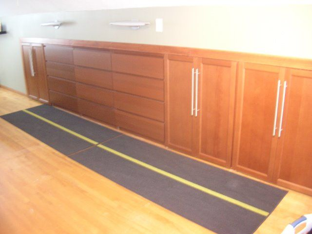 Sloped ceiling/wall closet storage built-ins using IKEA Malm dressers and cabinet doors.